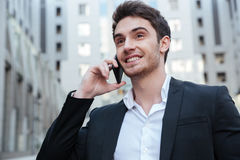 Portrait of businessman talking on phone. Portrait of smiling businessman talking on phone in the city Stock Images