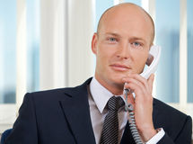 Portrait of businessman talking on telephone at office Royalty Free Stock Photography