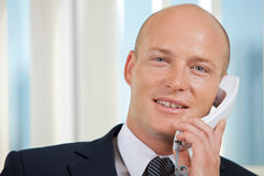 Portrait of businessman talking on telephone at office Royalty Free Stock Photo