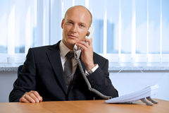 Portrait of businessman talking on telephone at office Royalty Free Stock Photos
