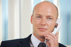 Portrait of businessman talking on telephone at office Royalty Free Stock Images
