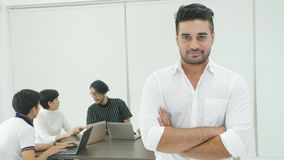Portrait of businessman with team of people working in background. Portrait of businessman with team of people working and talking in background during meeting stock video footage