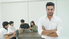Portrait of businessman with team of people working in background. Portrait of businessman with team of people working and talking in background during meeting stock footage