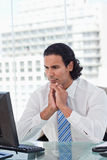 Portrait of a businessman thinking while using a computer Stock Photos
