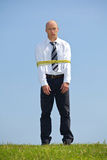 Portrait of businessman tied up with ropes in park Royalty Free Stock Image