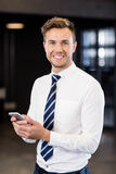 Portrait of businessman typing a text message in office. Portrait of businessman smiling and typing a message on his smartphone in office Royalty Free Stock Photography