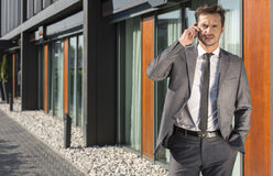Portrait of businessman using cell phone outside office Stock Photo