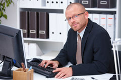 Portrait of a businessman using computer in office Stock Images
