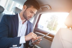 Portrait of businessman using digital tablet while travelling. In a car stock photo