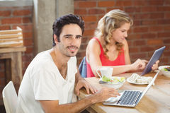 Portrait of businessman using laptop with colleague in background at office Royalty Free Stock Photo