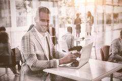 Portrait of businessman using laptop seen through glass Stock Images