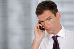 Portrait of businessman using mobile phone at office Stock Photography