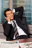 Portrait of businessman using telephone in office, smiling royalty free stock images