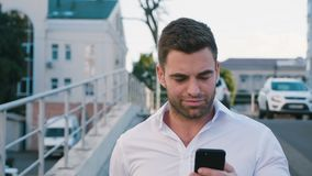 Portrait of Businessman Walking at parking near the Office Building. Looking at his Smartphone s Screen. White Shirt. Portrait of Young Businessman Walking at stock footage