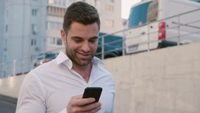 Portrait of Businessman Walking at parking near the Office Building. Looking at his Smartphone s Screen. White Shirt. Portrait of Young Businessman Walking at stock video