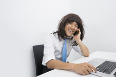Portrait of businessman wearing wig while using cell phone in office Stock Photos