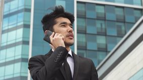 Portrait of businessman who makes phone calls stock video