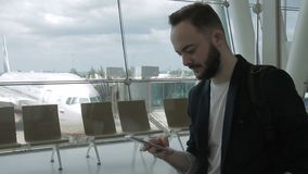 Portrait of businessman who is typing messege on his smartphone inside the airport. Man in balck jacket is standing near the big window and chairs and holding stock video footage