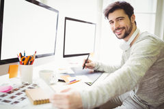 Portrait of businessman working at desk in office Stock Image