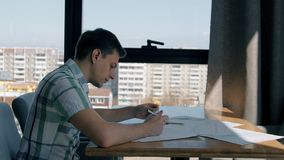 Portrait of businessman working on finance graphs in cafe with city view, slow motion. Concept of: cafe table, hand writing, paper work, graphs and charts stock video