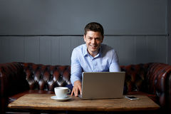 Portrait Of Businessman Working On Laptop In Internet Cafe Stock Photography