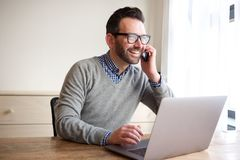 Businessman working on laptop and talking on cellphone. Portrait of businessman working on laptop and talking on cellphone Royalty Free Stock Photography