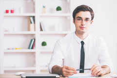 Portrait of businessman at workplace. Portrait of handsome young businessman sitting at modern workplace Royalty Free Stock Images