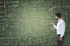 Portrait of businessman writing on blackboard stock photography