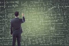 Portrait of businessman writing on blackboard Stock Images