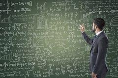 Portrait of businessman writing on blackboard Stock Photo