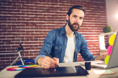 Portrait of businessman writing on graphic tablet while using laptop Royalty Free Stock Photos
