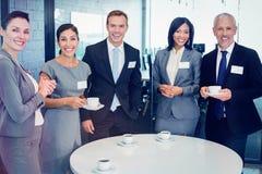 Portrait of businesspeople having tea during breaktime Stock Photos