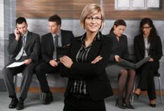 Portrait of businesswoman. Portrait of confident young businesswoman standing in office hallway, arms crossed, smiling royalty free stock photo