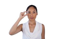 Portrait of businesswoman adjusting invisible eyeglasses Royalty Free Stock Image