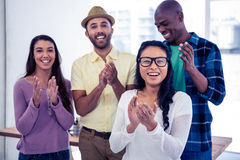 Portrait of businesswoman applauding with team Stock Image