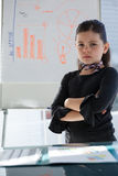 Portrait of businesswoman with arms crossed standing by whiteboard Royalty Free Stock Photos