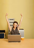 Portrait of businesswoman with arms raised, cup and laptop on desk Stock Photo