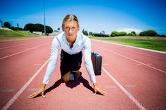 Portrait of businesswoman with briefcase ready to run. On running track Royalty Free Stock Image