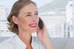Portrait of businesswoman calling in a bright office. And looking away Stock Image