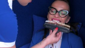 Woman choosing teeth color from samples before LED whitening teeth in dentistry.