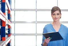 Portrait of a businesswoman with clipboard in warehouse. Close up portrait of a businesswoman with clipboard in warehouse Stock Photo