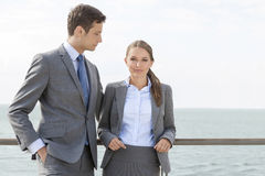 Portrait of businesswoman with coworker leaning on terrace railing against sky Royalty Free Stock Image