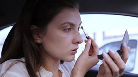 Portrait of a businesswoman doing makeup in a car. Applying eye shadows with a brush. Girl gets into the eye and winces
