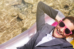 Portrait of businesswoman floating on pool raft. Portrait of young Caucasian businesswoman wearing suit and sunglasses lying with hands behind head on pool raft Stock Images