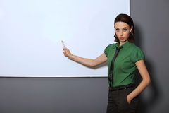 Portrait of businesswoman with hands in pockets pointing at whiteboard in office Royalty Free Stock Image