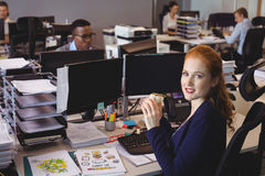 Portrait of businesswoman having snack while colleagues working in creative office. Portrait of businesswoman having snack at desk while colleagues working in stock photo