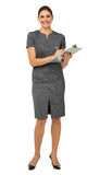 Portrait Of Businesswoman Holding Clipboard And Pen. Full length portrait of happy businesswoman holding clipboard and pen against white background. Vertical Stock Image