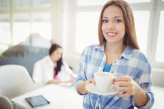 Portrait of businesswoman holding coffee cup at creative office Stock Photo