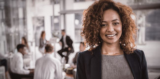 Portrait of businesswoman holding disposable coffee cup. Portrait of smiling businesswoman holding disposable coffee cup in office Stock Photos