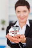Portrait of a businesswoman holding a miniature Stock Photos